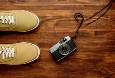 Cámara del vintage con las zapatillas de deporte en fondo de madera Fondo del recorrido horizontal Imagen de archivo libre de regalías