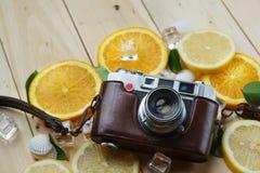 Cámara del vintage entre el cubo anaranjado fresco de las hojas de las cáscaras del mar del limón Imagen de archivo libre de regalías