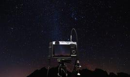 Cámara digital en el trípode de cámara que toma una foto de la vía láctea en la noche, con el cielo claro lleno de estrella Imagen de archivo libre de regalías