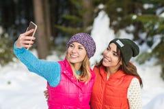 Cámara elegante del teléfono del control de la muchacha que tarda el invierno de Forest Young Woman Couple Outdoor de la nieve de fotografía de archivo libre de regalías