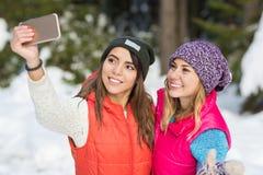 Cámara elegante del teléfono del control de la muchacha que tarda el invierno de Forest Young Woman Couple Outdoor de la nieve de imagen de archivo libre de regalías