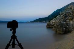 Cámara en el trípode con puesta del sol sobre el mar en el fondo/Podgora, Croacia Imagenes de archivo