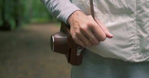 Cámara femenina del holdinga de la mano en una caja marrón en su hombro en bosque en primavera almacen de metraje de vídeo