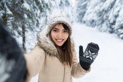 Cámara hermosa asiática joven de la sonrisa de la mujer que toma la foto de Selfie en la nieve Forest Girl Outdoors del invierno imágenes de archivo libres de regalías