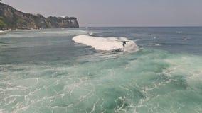 Cámara lenta aérea de Uluwatu que practica surf Bali almacen de video
