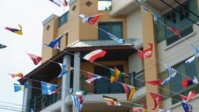 Cámara lenta, banderas suspendidas en cuerda fina en el aire sobre la calle Símbolos de diversas naciones que agitan en el viento almacen de video