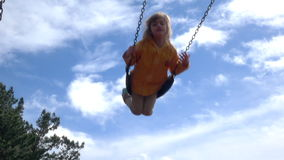 Cámara lenta borrosa de la muchacha feliz que balancea en el patio almacen de video