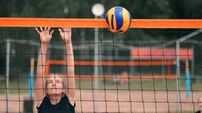 Cámara lenta, cierre para arriba, ángulo bajo: manos de la hembra joven irreconocible 'que juegan voleibol en la red Jugador ofen almacen de video