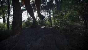 CÁMARA LENTA, CIERRE PARA ARRIBA: Cima de la montaña que sube del caminante masculino valeroso irreconocible, caminando de rastro almacen de metraje de vídeo