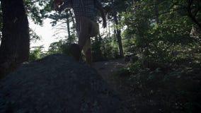 CÁMARA LENTA, CIERRE PARA ARRIBA: Cima de la montaña que sube del caminante masculino valeroso irreconocible, caminando de rastro metrajes
