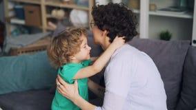 Cámara lenta de amar al pequeño niño que abraza a su madre que expresa amor en casa almacen de video