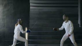 A cámara lenta de dos cercadores hombre y mujer tenga cercado del partido dentro almacen de metraje de vídeo