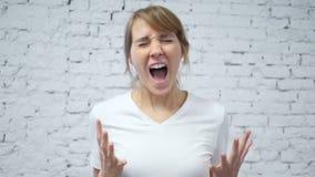Cámara lenta de gritar a la mujer joven trastornada en estudio almacen de video