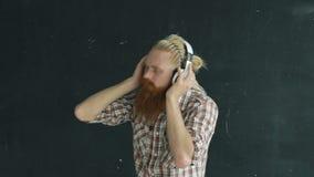 A cámara lenta de hombre joven barbudo en los auriculares que bailan mientras que escuche la música en fondo negro almacen de metraje de vídeo