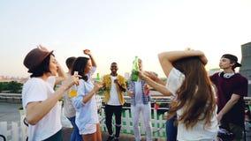 Cámara lenta de hombres jovenes alegres y de mujeres que bailan en el partido al aire libre en el tejado que sostiene las botella almacen de video