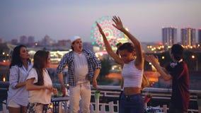 Cámara lenta de hombres jovenes atractivos y de mujeres que bailan en el tejado que relaja y que se divierte con la risa hermosa  almacen de metraje de vídeo