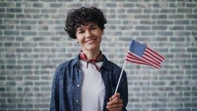 Cámara lenta de la bandera americana orgullosa de la tenencia del ciudadano que sonríe en fondo del ladrillo almacen de video