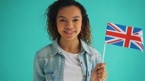 C?mara lenta de la bandera bonita de la tenencia de la mujer de la raza mixta de la sonrisa de Inglaterra almacen de metraje de vídeo