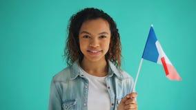 C?mara lenta de la bandera francesa femenina de la tenencia del patriota de la sonrisa de Francia almacen de metraje de vídeo
