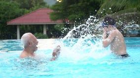 Cámara lenta de la familia asiática feliz que juega en piscina