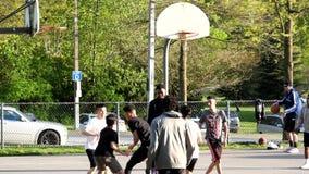 Cámara lenta de la gente que juega a baloncesto en el parque metrajes