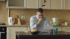 Cámara lenta de la letra de la lectura del hombre joven del trastorno con la cuenta sin pagar en la cocina en casa