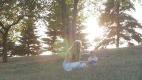 Cámara lenta de la madre y de la hija en puesta del sol de la llamarada en parque almacen de video