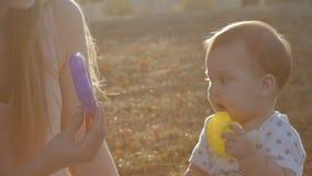 Cámara lenta de la madre y de la hija en puesta del sol de la llamarada en parque metrajes