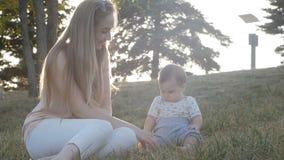 Cámara lenta de la madre y de la hija en puesta del sol de la llamarada en parque almacen de metraje de vídeo