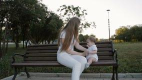 Cámara lenta de la madre y de la hija que se sientan en el banco en parque almacen de video