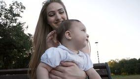 Cámara lenta de la madre y de la hija que se sientan en el banco en parque almacen de metraje de vídeo