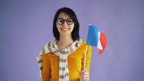 Cámara lenta de la morenita joven linda en los vidrios que celebran la sonrisa francesa de la bandera metrajes