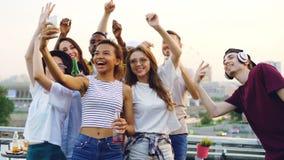 Cámara lenta de la muchacha afroamericana atractiva que toma el selfie en el partido al aire libre con sus amigos que bailan y qu metrajes