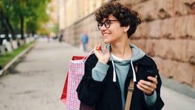 Cámara lenta de la muchacha bonita con los panieres de papel brillantes que camina en la calle y que usa el smartphone entonces q almacen de video