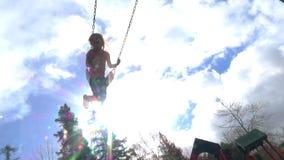 Cámara lenta de la muchacha feliz que balancea en el patio almacen de video