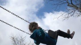 Cámara lenta de la muchacha feliz que balancea en el patio metrajes
