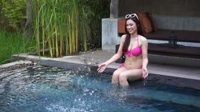 Cámara lenta de la mujer en piscina y jugar el chapoteo del agua metrajes