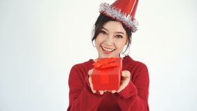 Cámara lenta de la mujer feliz con el sombrero y sostener una caja de regalo roja de la Navidad en un gesto del donante