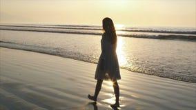 Cámara lenta de la mujer que camina descalzo en orilla de mar mojada durante puesta del sol almacen de metraje de vídeo