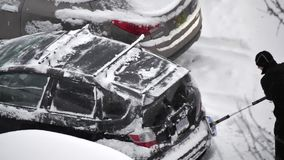 Cámara lenta de la nieve y del hielo de limpieza de la gente de su ventana del escudo de viento del coche