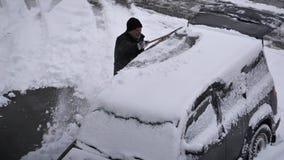 Cámara lenta de la nieve y del hielo de la limpieza del hombre de su ventana del escudo de viento del coche