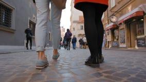 Cámara lenta de la opinión trasera los pies de dos señoras jovenes que caminan en la ciudad vieja almacen de metraje de vídeo