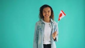 Cámara lenta de la señora afroamericana bonita que celebra la bandera canadiense y la sonrisa almacen de video