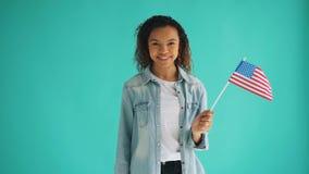 Cámara lenta de la señora afroamericana con la bandera de los E.E.U.U. que sonríe mirando la cámara metrajes