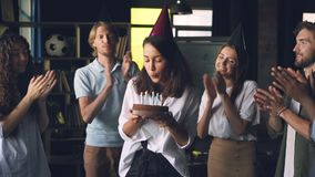Cámara lenta de la señora joven feliz que sostiene la torta de cumpleaños y que sopla las velas que se colocan en oficina con los metrajes