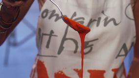 Cámara lenta de la sustancia anaranjada que gotea abajo de la cuchara en fondo borroso almacen de metraje de vídeo