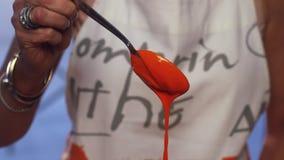 Cámara lenta de la sustancia anaranjada que se derrama sobre la cuchara metálica y que gotea abajo metrajes