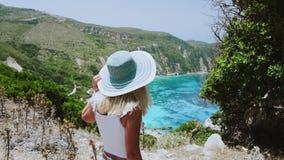 Cámara lenta de las mujeres rubias del jung hermoso con el sombrero del sol que caminan hacia la playa y enjoing su vocación feli almacen de video