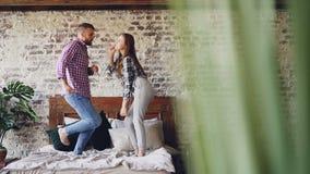 Cámara lenta de los amantes jovenes felices que bailan en la cama matrimonial que se divierte en dormitorio y que ríe negligentem almacen de metraje de vídeo