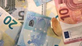 Cámara lenta de los billetes de banco euro de la UE de la moneda de Bitcoin que gira almacen de metraje de vídeo